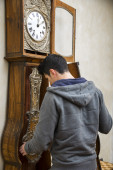 Young man winding the mechanism on a clock — Stock Photo