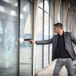 Постер, плакат: Detective or policeman firing a gun to a window glass