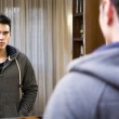 Handsome young man looking at himself in mirror — Stock Photo #61395203