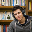 Attractive young man sitting listening to music smiling — Stock Photo #61395359
