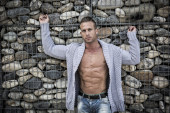 Muscular man in front of stone wall — Stock Photo