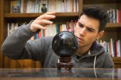 Young man predicting the future by looking into crystal ball — Stock Photo