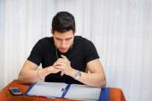 Young man studying or working at home with diabolical face — Stock Photo