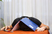 Tired, exhausted or despondent young man with a folder over his head — Stock Photo