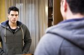Handsome young man looking at himself in mirror — Stock Photo