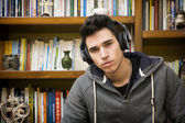 Attractive young man at home listening to music on headphones — Stock Photo