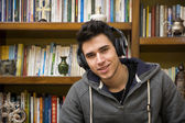 Attractive young man sitting listening to music smiling — Stock Photo