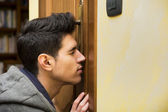 Young man spying through the keyhole of a door — Stock Photo