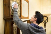 Young man checking a pendulum and winding the mechanism — Stock Photo