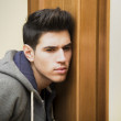 Young man listening in behind a door — Stock Photo #61667363