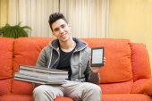 Young man showing difference between ebook reader and heavy books — Stockfoto