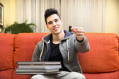 Young man showing difference between USB drive and heavy books — Stock Photo