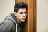 Young man listening in behind a door — Stock Photo