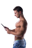 Male bodybuiler holding ebook reader or tablet PC — Стоковое фото