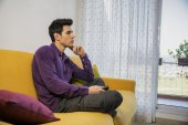 Man sitting on couch watching television — Stock Photo