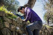 Young man climbing stone wall — Stock Photo