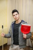 Handsome Young Man Holding Dust Pan and a Broom — Stock fotografie