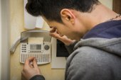 Young man checking the speaker phone and alarm — Stock Photo