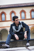 Trendy man sitting outdoor in old historical building — Stock Photo