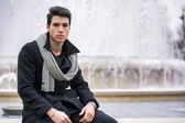 Young man sitting outdoor in front of big fountain — Stock Photo