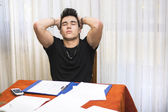Tired or despondent young man doing homework — Stock Photo
