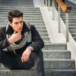 Trendy handsome man sitting on a long staircase — Stock Photo #67955593
