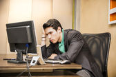 Preoccupied, worried young male worker staring at computer — Stock Photo