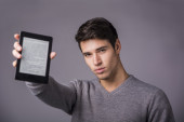 Young man holding and showing ebook reader — 图库照片