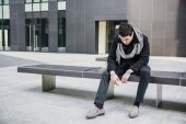 Trendy handsome young man sitting on stone bench — Stock Photo