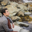 Young man outdoor sitting alone at river or water stream — Stock Photo #68758739