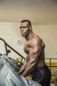 Black male bodybuilder exercising on treadmill — Stock Photo