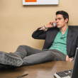 Young businessman at desk talking on phone — Stock Photo #69496209