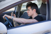 Young Man Using his Cell Phone Driving a Car — Stock fotografie