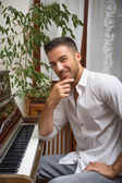 Handsome male artist at wooden upright piano — Stock Photo