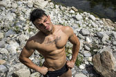 Muscular shirtless young man in nature — Stock Photo