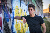 Attractive young man standing against colorful graffiti wall — Stock Photo