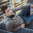 Handsome young man, sitting and leaning on metal grid stairs — Stok fotoğraf #70741233