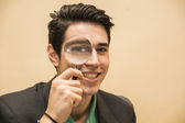 Handsome young man holding a magnifying glass — Stock Photo