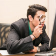 Businessman searching through magnifying glass in computer — Fotografia Stock  #71854141