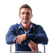 Smiling young man sitting on chair backwards — Stock Photo #71862149