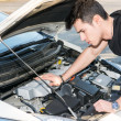 Handsome young man trying to repair a car engine — Stock Photo #71866127
