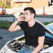 Man trying to repair a car and seeking help — Stock Photo #71866809