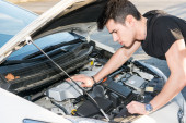 Handsome young man trying to repair a car engine — Stock Photo