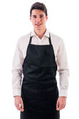 Young chef or waiter wearing black apron — Stock Photo