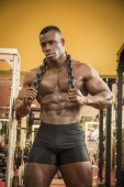 Attractive hunky black male bodybuilder posing with iron chains — Stock Photo