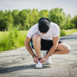 Handsome young man tying sports shoes before going running — Stock Photo #72124719