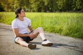 Handsome young man injured while running and jogging on road — Stock Photo