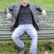 Handsome blond young man sitting on park bench — Stock Photo #72133467