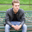 Handsome blond young man sitting on park bench — Stock Photo #72133949