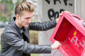 Handsome young male vandal breaking public property — Stock Photo